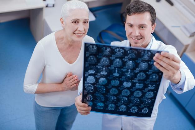 Mulher idosa simpática e alegre olhando para a foto do raio x e se sentindo aliviada por não ter desvios físicos