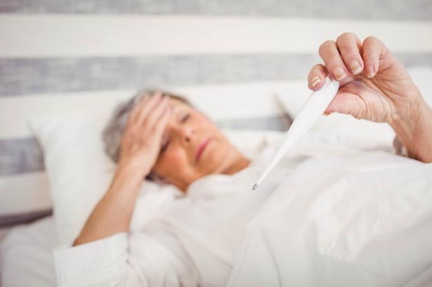 Mulher idosa sofre de febre, verificando sua temperatura no termômetro