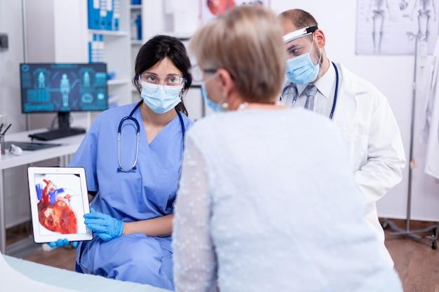 Mulher idosa sofrendo de arritmias e conversando com cardiologista durante exame no hospital usando máscara facial contra coronavírus