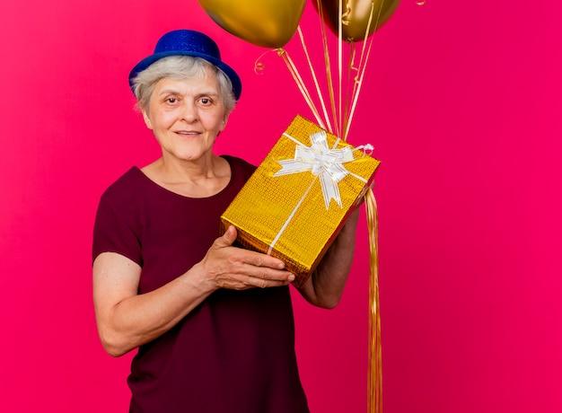 Mulher idosa sorridente com chapéu de festa segurando balões de hélio e uma caixa de presente isolada na parede rosa