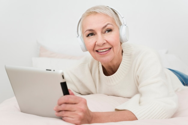 Mulher idosa sorridente com fones de ouvido segurando o tablet