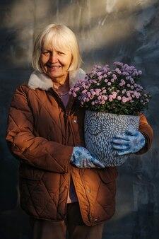 Mulher idosa sorridente com roupa quente casual segurando um vaso com flores cor de rosa desabrochando