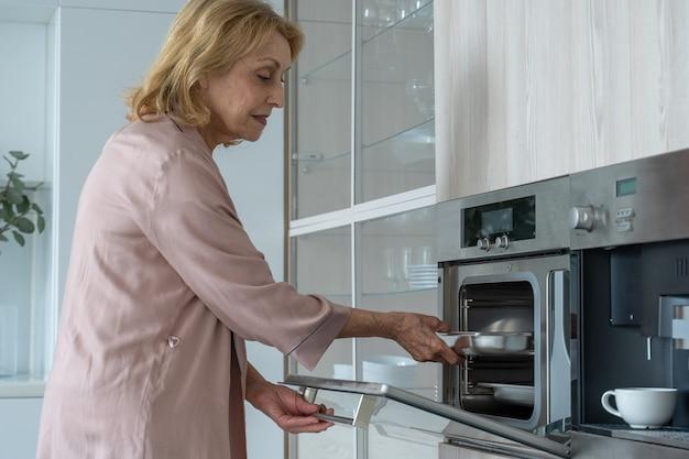 Mulher idosa sorridente fazendo doces em casa tirando os doces do forno de uma senhora idosa em