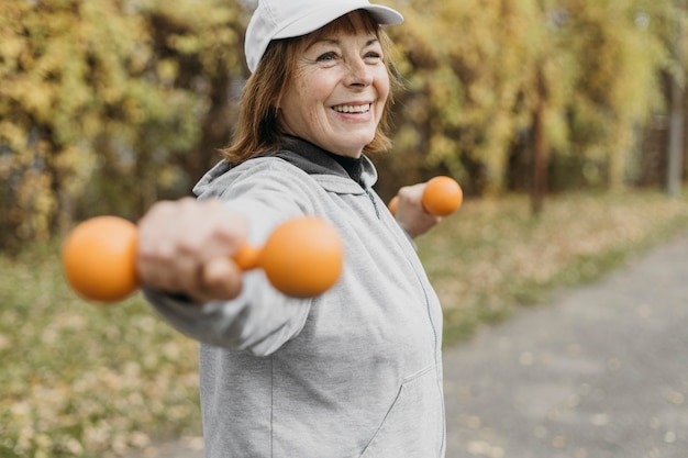 Mulher idosa sorridente fazendo exercícios com pesos ao ar livre