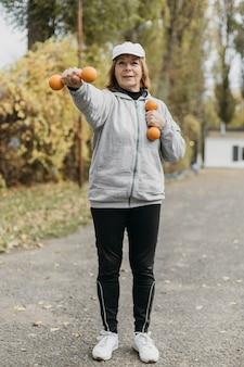 Mulher idosa sorridente fazendo exercícios com pesos lá fora