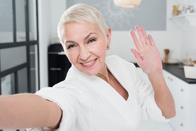 Mulher idosa sorridente feliz posando em roupão