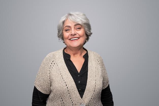 Mulher idosa sorridente, olhando para a frente