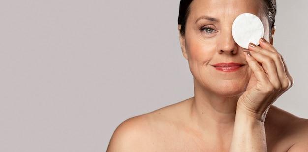 Mulher idosa sorridente posando com almofada de algodão para remoção de maquiagem e espaço de cópia