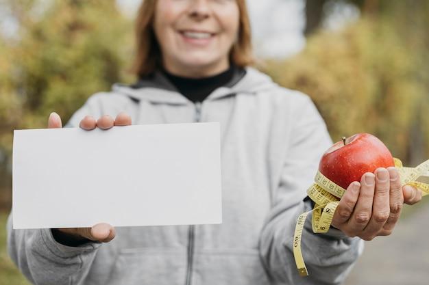 Mulher idosa sorridente segurando maçã e papel ao ar livre enquanto se exercita
