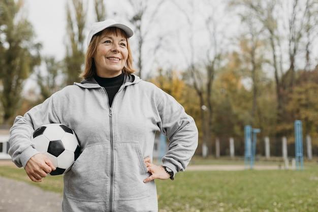 Mulher idosa sorridente segurando uma bola de futebol ao ar livre enquanto se exercita