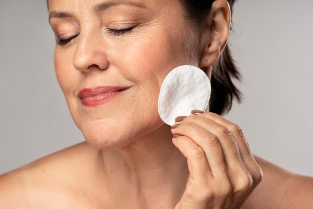 Mulher idosa sorridente usando almofada de algodão para remoção de maquiagem