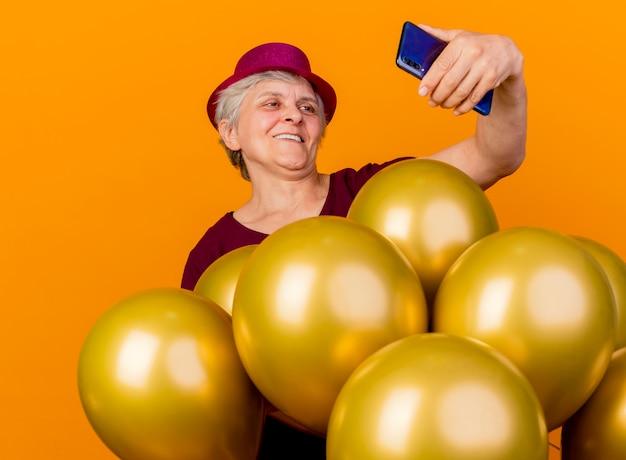 Mulher idosa sorridente usando chapéu de festa com balões de hélio olhando para o telefone isolado na parede laranja