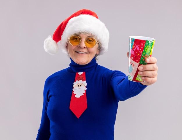 Mulher idosa sorridente usando óculos de sol com chapéu e gravata de papai noel segurando um copo de papel