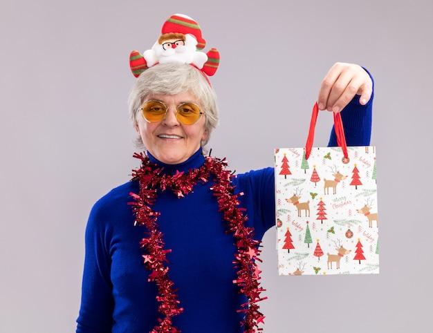 Mulher idosa sorridente usando óculos de sol com faixa de papai noel e guirlanda em volta do pescoço segurando uma sacola de papel para presente isolada na parede branca com espaço de cópia