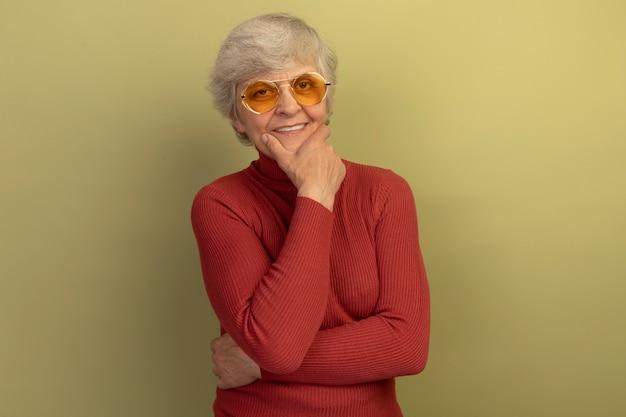 Mulher idosa sorridente, vestindo um suéter vermelho de gola alta e óculos de sol, olhando para a frente, mantendo a mão no queixo isolada na parede verde oliva com espaço de cópia