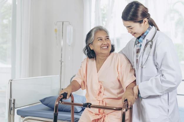 Mulher idosa sorrindo com jovem médico feminino visitando paciente sênior na enfermaria do hospital