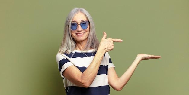 Mulher idosa sorrindo, sentindo-se feliz, despreocupada e satisfeita, apontando para um conceito ou ideia no espaço da cópia ao lado