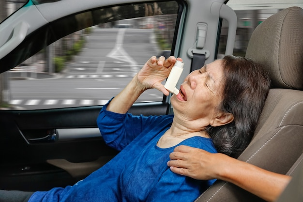 Mulher idosa sufocando e segurando um spray anti-asma dentro do carro no caminho
