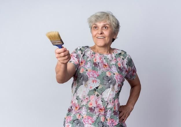 Mulher idosa surpreendida segura e aponta para a frente com um pincel isolado na parede branca