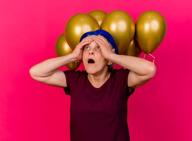 Mulher idosa surpresa com chapéu de festa coloca as mãos na testa em frente a balões de hélio