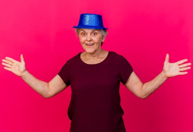 Mulher idosa surpresa com chapéu de festa fica de mãos abertas, olhando para a frente, isolada na parede rosa