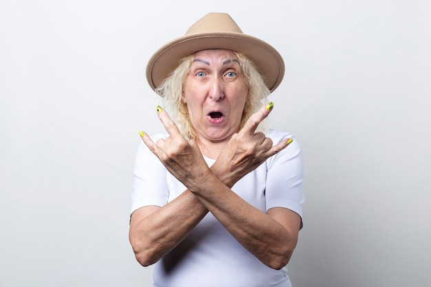 Mulher idosa surpresa com chapéu mostra gesto de chifre de balancim sobre fundo claro.