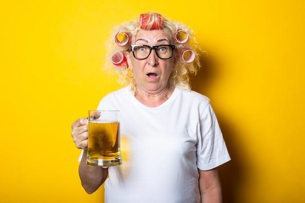 Mulher idosa surpresa com rolos de cabelo com um copo de cerveja em uma superfície amarela