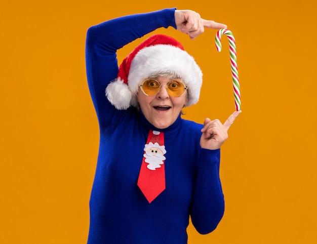 Mulher idosa surpresa em óculos de sol com chapéu de papai noel e gravata de papai noel segurando o bastão de doces com dois dedos isolados em um fundo laranja com espaço de cópia