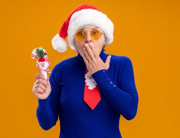 Mulher idosa surpresa usando óculos de sol com chapéu de papai noel e gravata de papai noel coloca a mão na boca e segura o bastão de doces isolado em um fundo laranja com espaço de cópia