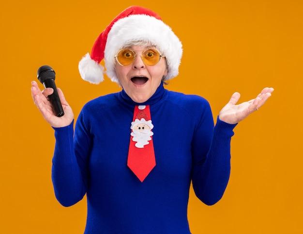 Mulher idosa surpresa usando óculos de sol com chapéu de papai noel e gravata de papai noel segurando o microfone isolado em um fundo laranja com espaço de cópia
