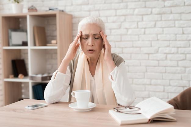 Mulher idosa tem dor de cabeça. conceito de saúde de idosos.