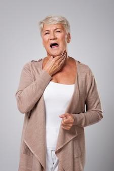 Mulher idosa tem grandes problemas com dor de garganta