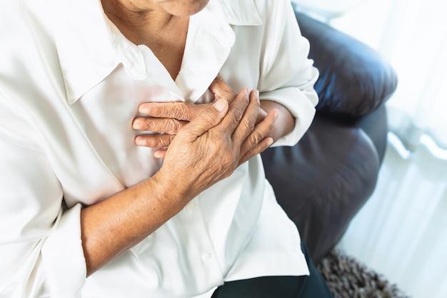 Mulher idosa tendo ataque cardíaco e agarrando o peito