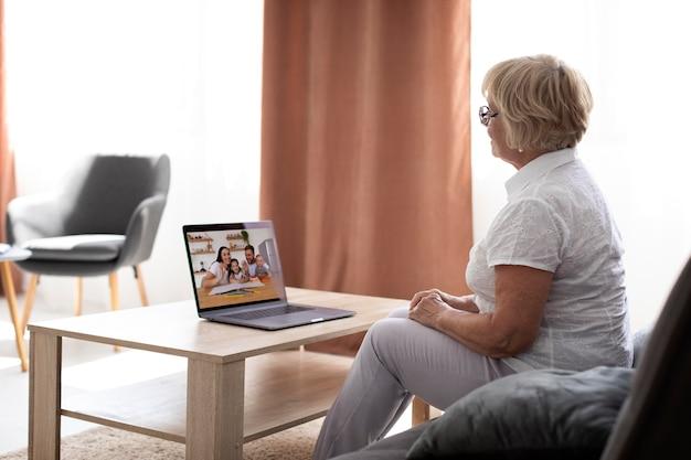 Mulher idosa tendo uma videochamada com a família