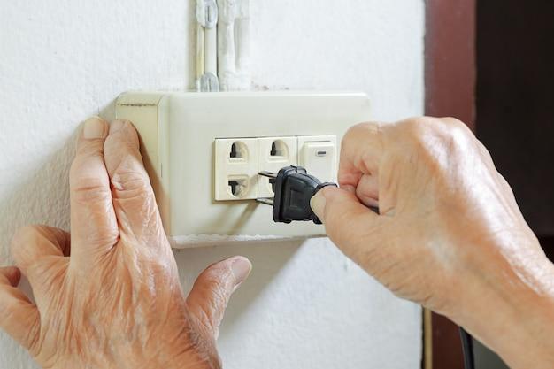 Mulher idosa tentando conectar o cabo à tomada elétrica