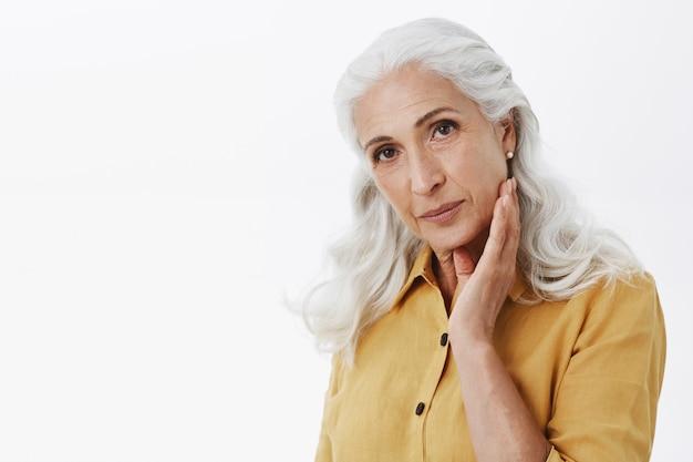 Mulher idosa, terna e sonhadora, tocando suavemente a bochecha, cuidando da pele e das rugas