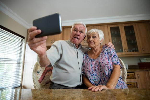 Mulher idosa tirando selfie do celular na cozinha de casa