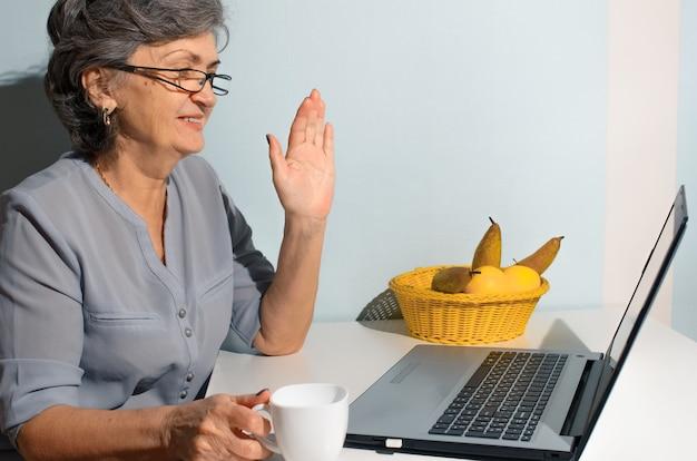 Mulher idosa tomando café e falando online no laptop em casa. conceito de videochamada, novo normal, auto-isolamento