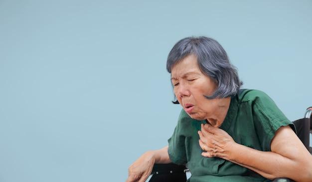 Mulher idosa tosse, engasgo na cadeira de rodas