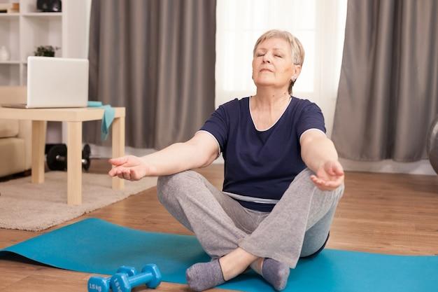 Mulher idosa tranquila com os olhos fechados fazendo ioga na sala de estar