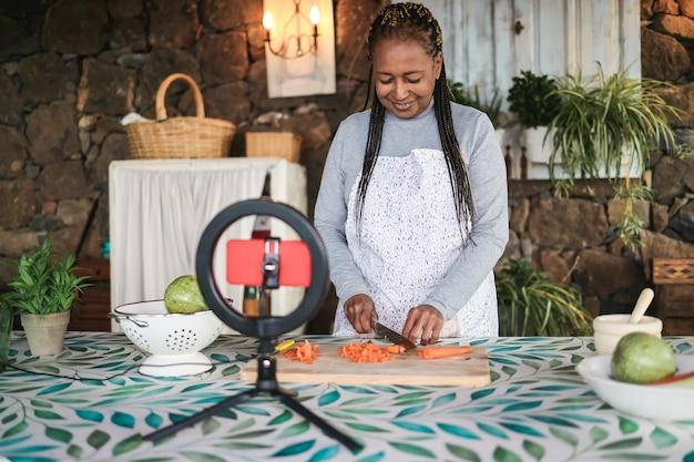 Mulher idosa transmitindo aula virtual de culinária vegetariana online ao ar livre em casa