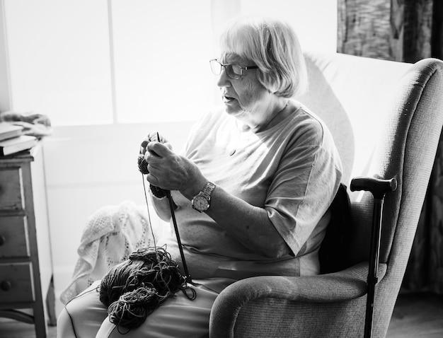 Mulher idosa tricotando em casa