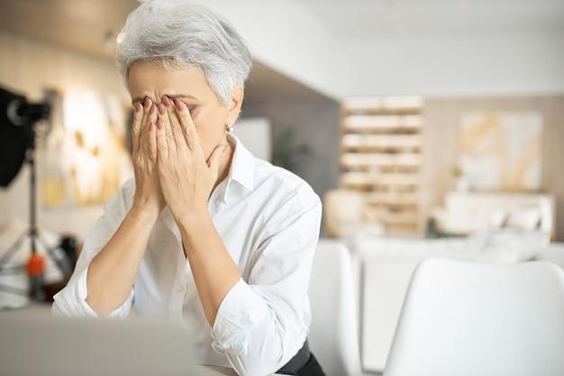 Mulher idosa triste com cabelos grisalhos trabalhando em um laptop, esfregando os olhos ou escondendo as lágrimas, cheia de pensamentos inquietos