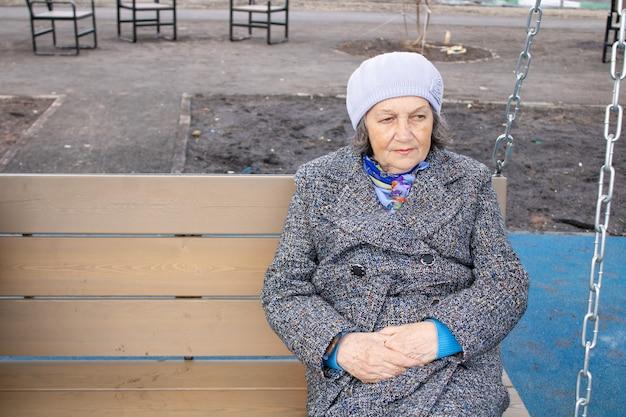 Mulher idosa triste descansando em um balanço ao ar livre