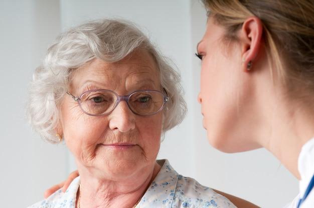 Mulher idosa triste e solitária com enfermeira