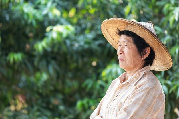 Mulher idosa um fazendeiro que sorri e que realiza no jardim.