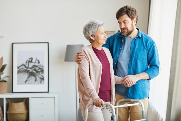 Mulher idosa usando andador e conversando com seu cuidador, ajudando-a durante a reabilitação