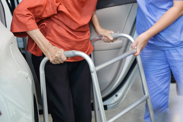 Mulher idosa usando andador enquanto sai do carro com cuidador