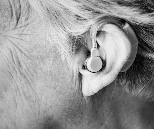 Mulher idosa usando aparelho auditivo
