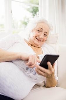 Mulher idosa, usando, dela, smartphone, mentindo sofá